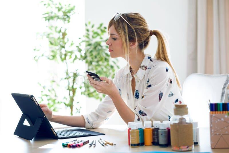 Vrolijke mooie jonge ontwerpervrouw die met haar digitale tablet werken terwijl het houden van haar mobiele telefoon op het kanto stock afbeeldingen