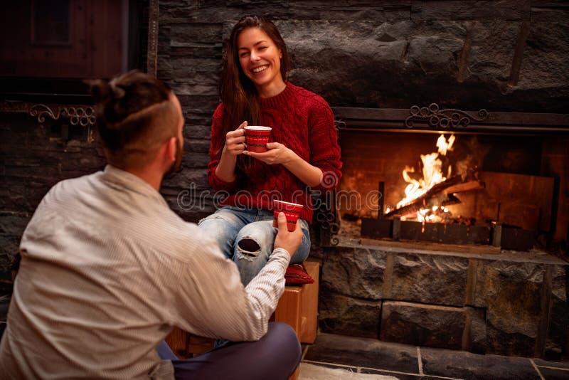 Vrolijke mooie jonge paar het drinken coffeein voorzijde van brand royalty-vrije stock afbeelding