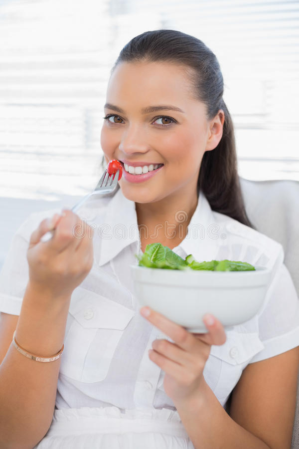 Vrolijke mooie vrouw die gezonde saladezitting op bank eten stock foto