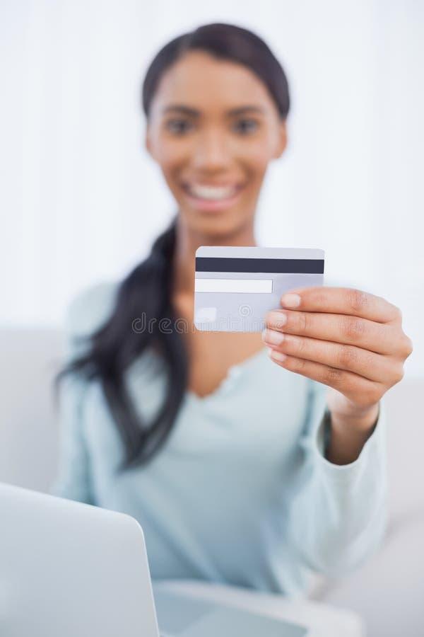 Vrolijke mooie vrouw die haar laptop met behulp van online te kopen royalty-vrije stock afbeeldingen