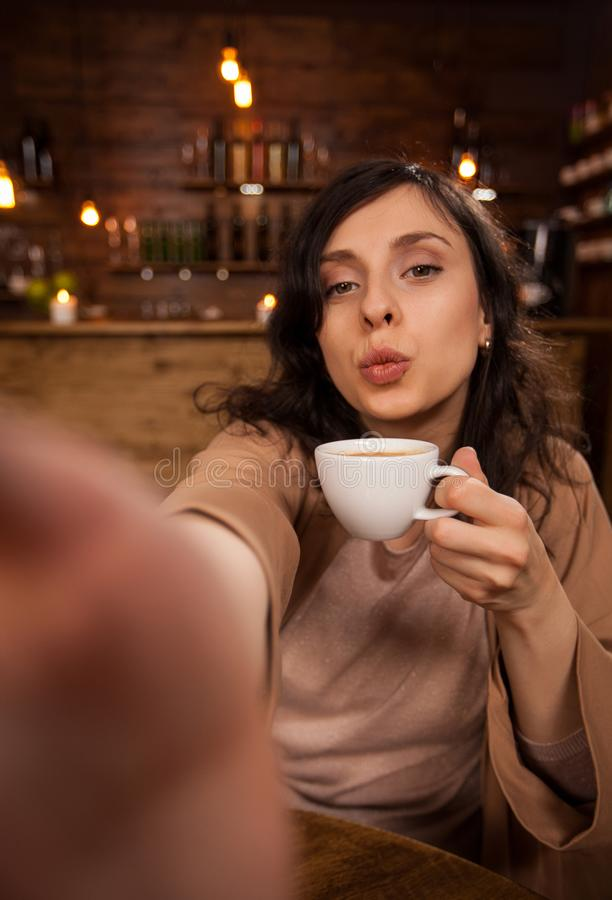 Vrolijke mooie vrouw die het kussen geven en een zelf-portret met smartphone in een koffiewinkel nemen royalty-vrije stock afbeeldingen