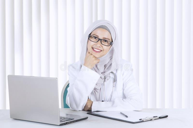 Vrolijke Moslimarts die in de kliniek werken royalty-vrije stock afbeelding