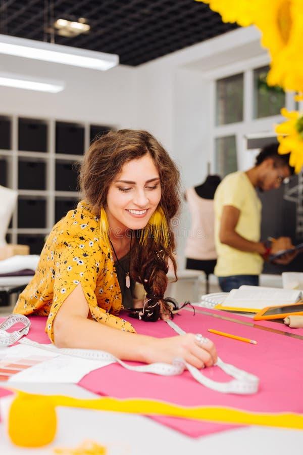 Vrolijke naaister die terwijl het doen van de noodzakelijke meting glimlachen stock foto