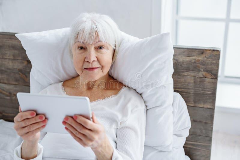 Vrolijke oma die haar tablet in het ziekenhuis houden stock foto