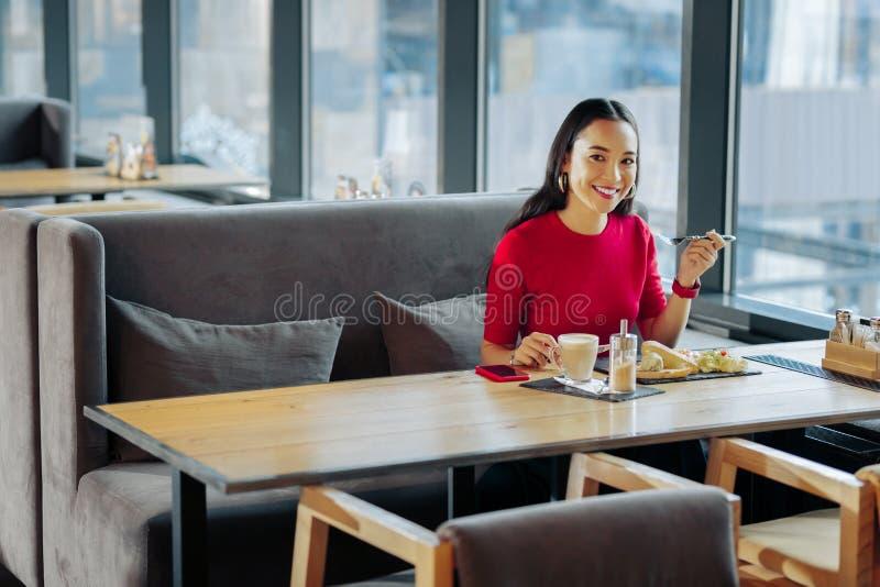 Vrolijke onderneemster met rode lippen die rust in restaurant hebben stock foto