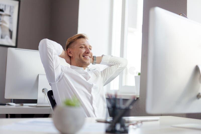 Vrolijke ondernemer bij computer stock foto