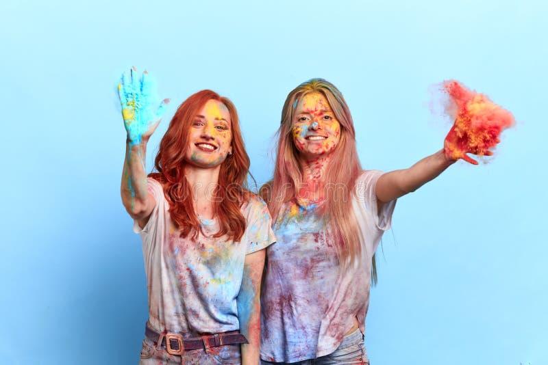 Vrolijke ontzagwekkende grappige vrouwelijke vrienden die kleurrijk poeder werpen bij holifestival royalty-vrije stock foto's