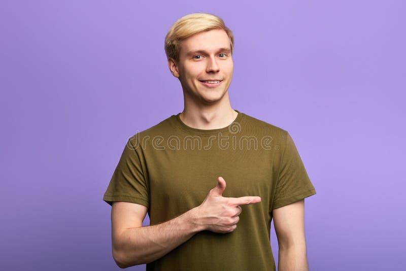 Vrolijke ontzagwekkende mens die weg op violette achtergrond richten royalty-vrije stock afbeelding