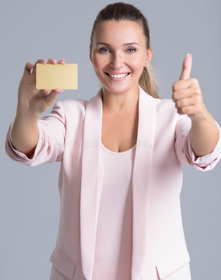 Vrolijke opgewekte verraste jonge vrouw met creditcard over whi stock fotografie