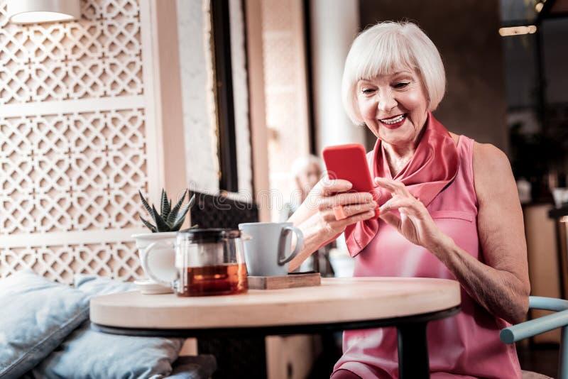 Vrolijke oude dame die comfortabel in een koffie zitten royalty-vrije stock foto's