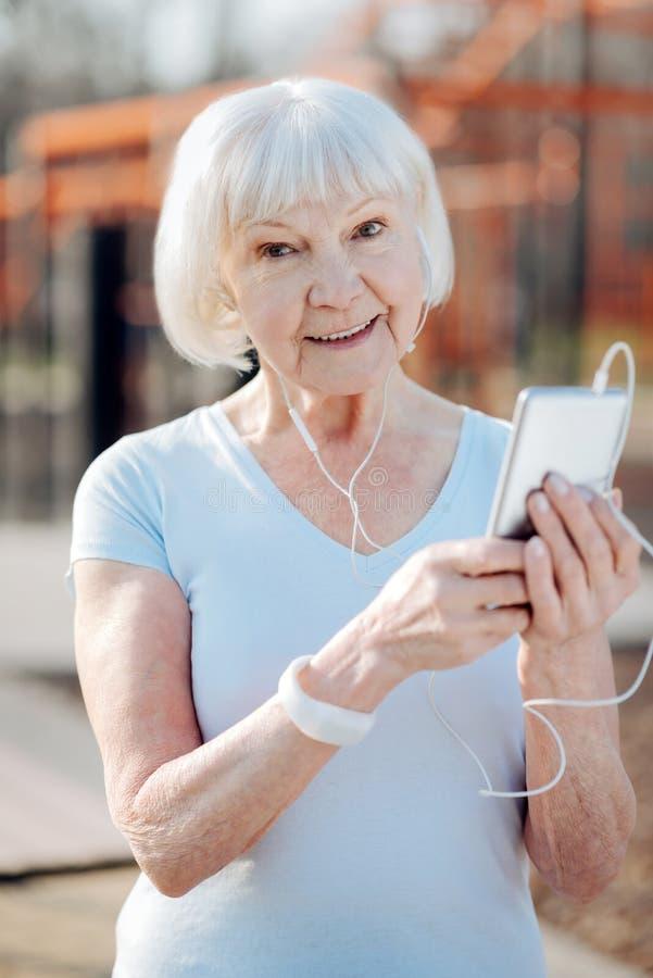 Vrolijke oude vrouw die aan muziek luisteren royalty-vrije stock foto's