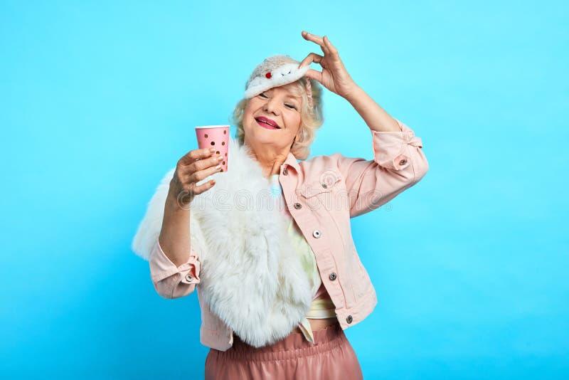 Vrolijke oude vrouw die beschikbare plasic kop van T-stuk houden stock fotografie