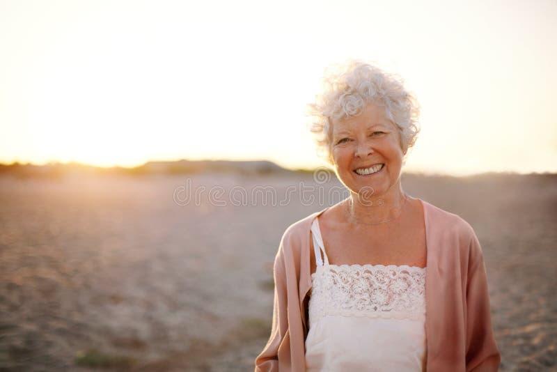 Vrolijke oude vrouw die zich op het strand bevinden stock afbeeldingen