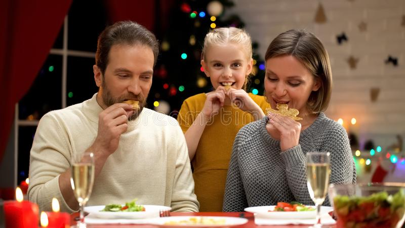 Vrolijke ouders en dochter die koekjes op Kerstmisvooravond samen eten, vakantie royalty-vrije stock fotografie