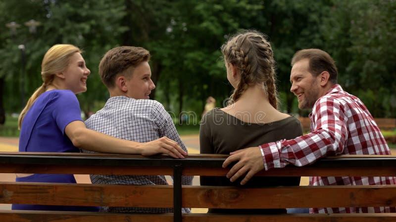 Vrolijke ouders en hun tienerkinderen die weekend op bank in park plannen royalty-vrije stock afbeeldingen