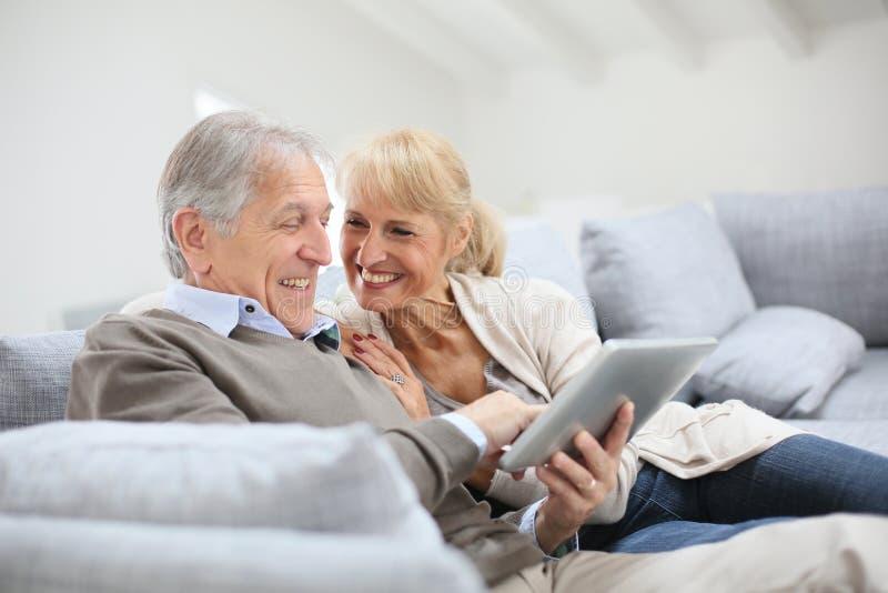Vrolijke oudste die coupl met tablet op bank genieten van stock foto's