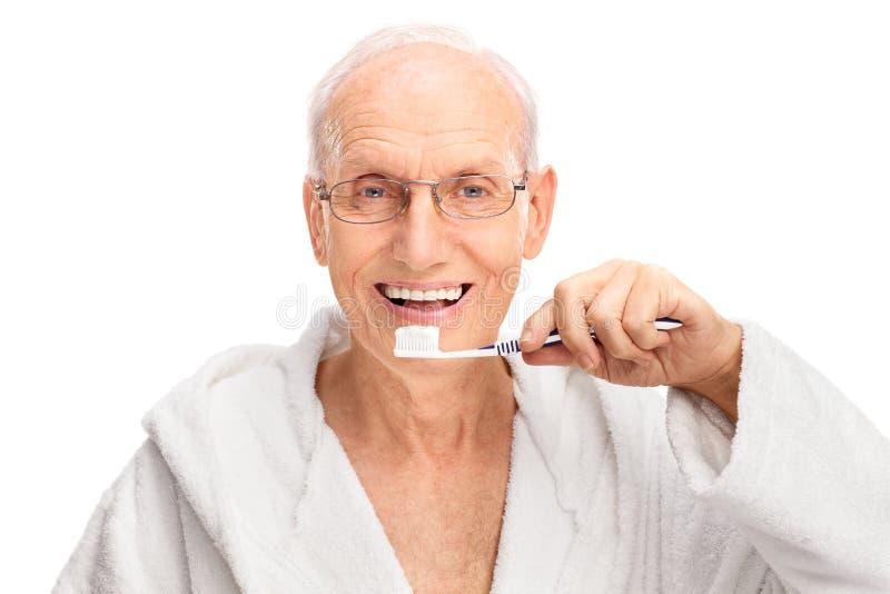 Vrolijke oudste die zijn tanden borstelen royalty-vrije stock afbeeldingen