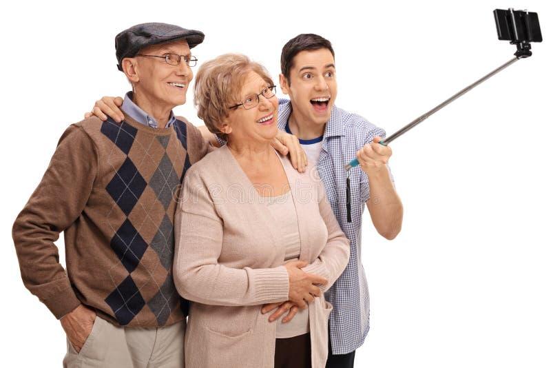 Vrolijke oudsten en een jonge mens die een selfie met een stok nemen royalty-vrije stock foto's