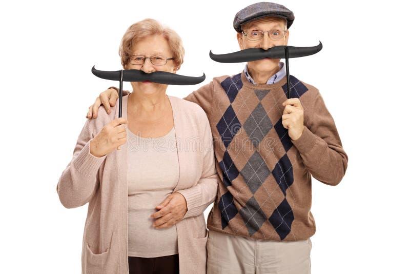 Vrolijke oudsten met grote valse snorren stock foto's