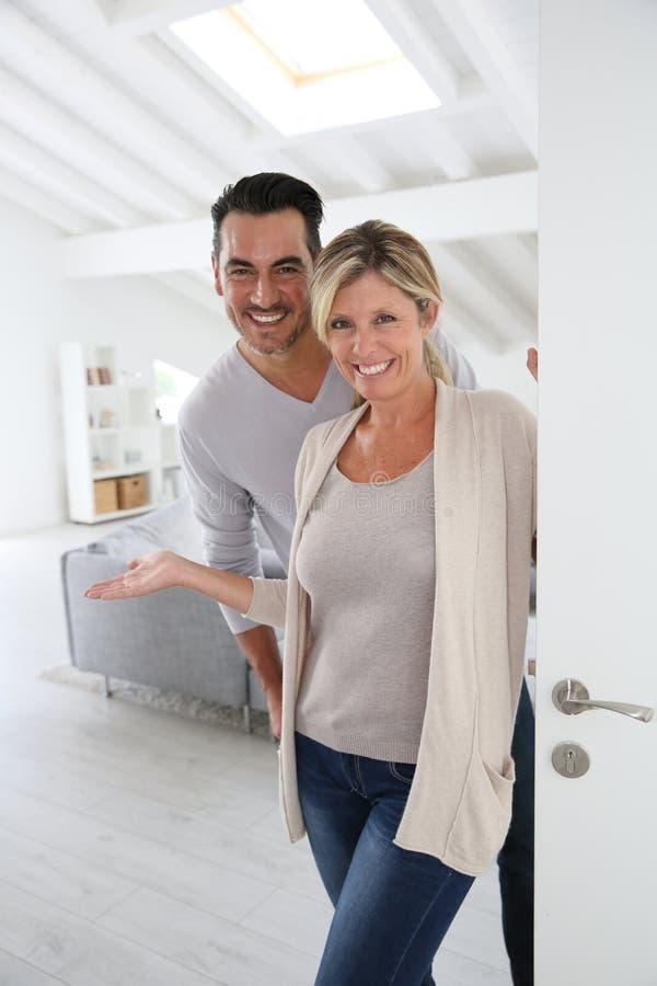 Vrolijke paar welkom hetende gasten aan hun nieuw huis royalty-vrije stock foto's