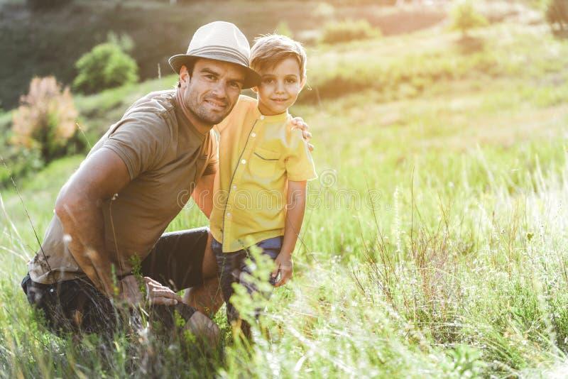 Vrolijke papa en zoons het besteden tijd in openlucht stock fotografie