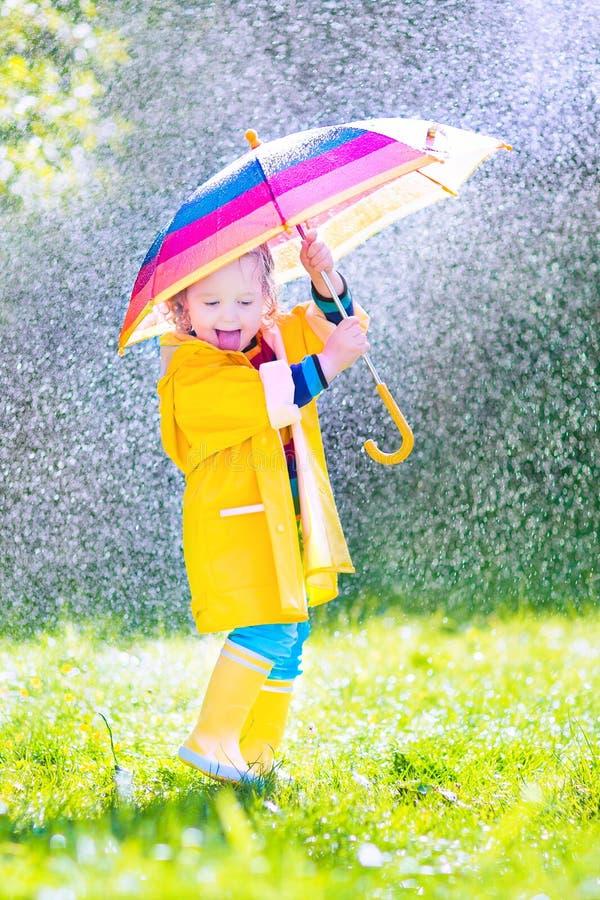 Vrolijke peuter met paraplu het spelen in de regen stock afbeelding
