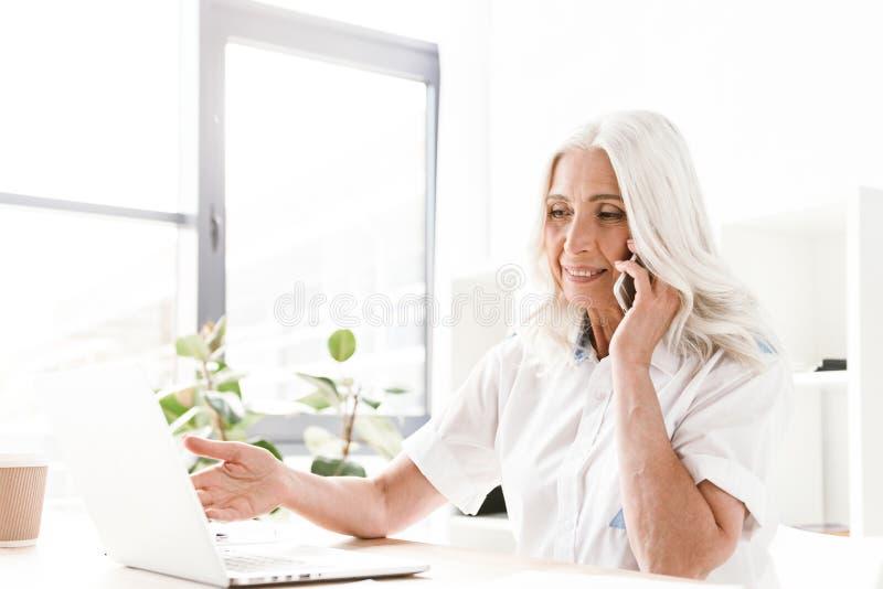 Vrolijke positieve rijpe vrouw die door mobiele telefoon spreken die laptop computer met behulp van stock foto