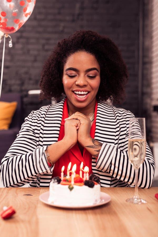 Vrolijke positieve vrouw die de kaarsen voorbereidingen treffen te blazen stock foto's