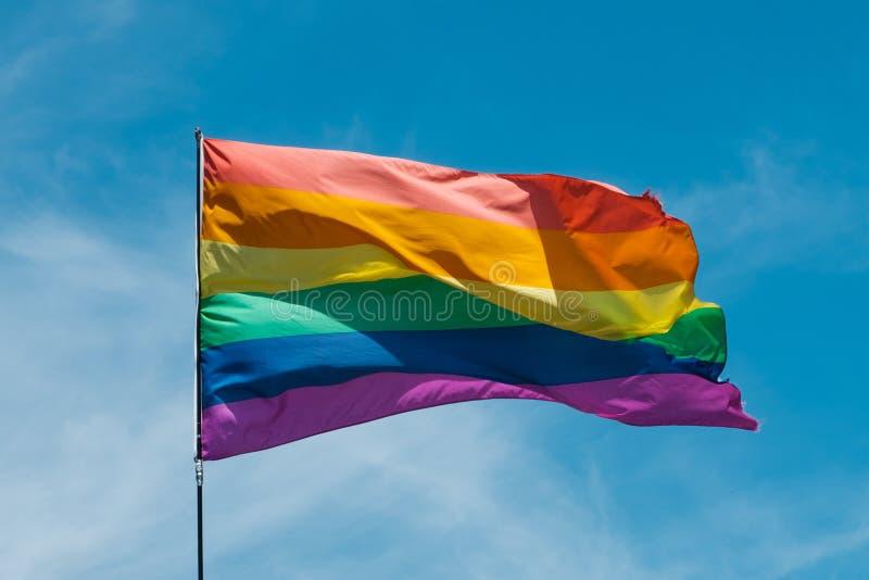 Vrolijke regenboogvlag die met blauwe hemelachtergrond golven - symbool van Gay Pride stock afbeelding