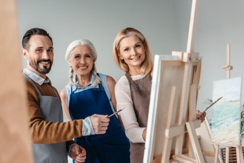vrolijke rijpe kunstenaars die bij camera glimlachen terwijl samen het schilderen royalty-vrije stock afbeelding