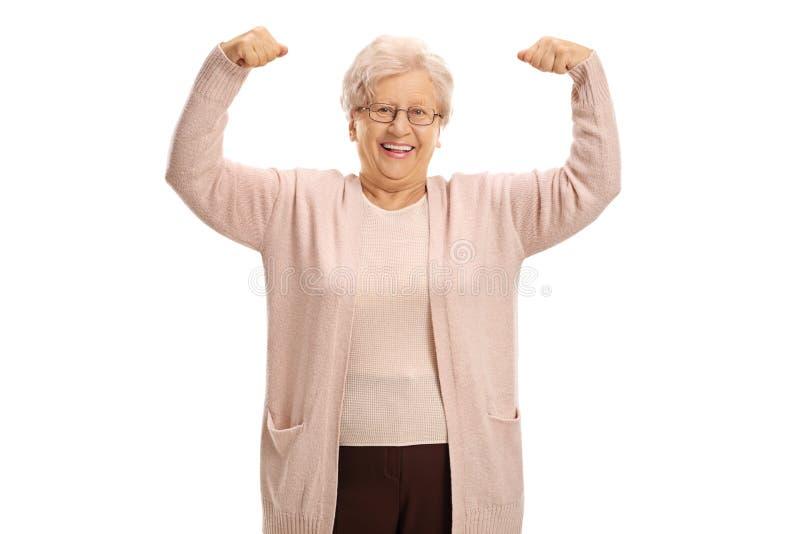 Vrolijke rijpe vrouw die haar spieren buigen stock foto's