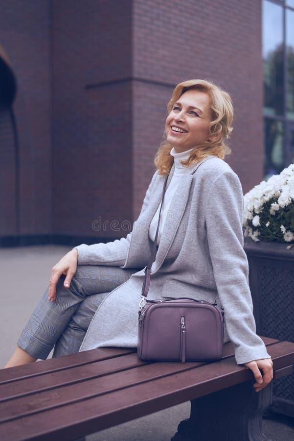Vrolijke rijpe vrouw die upwards terwijl het zitten op de bank kijkt royalty-vrije stock foto