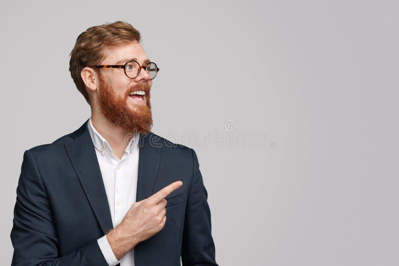 Vrolijke rode haired zakenman die op exemplaarruimte richten stock afbeeldingen