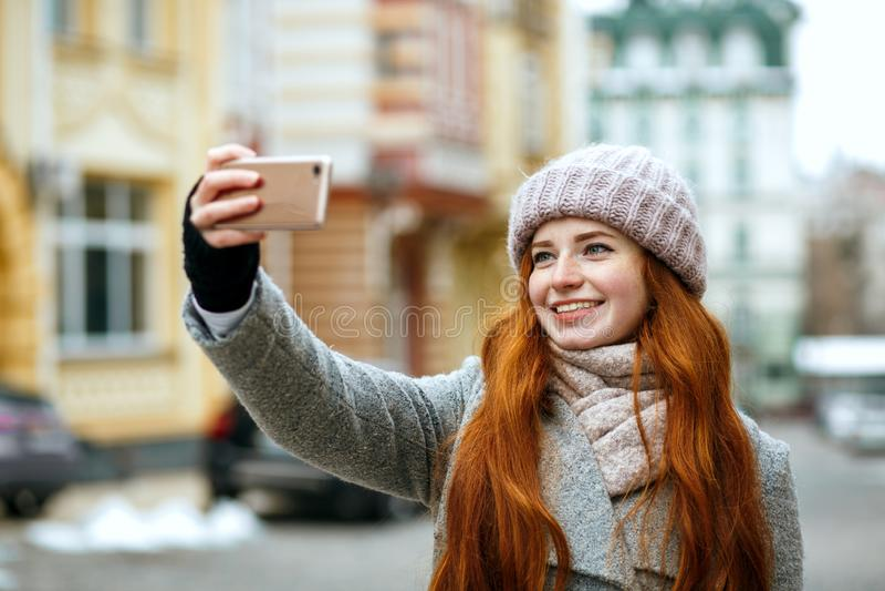 Vrolijke rode hoofdvrouw in de winterkleding die selfie op haar m nemen stock afbeelding