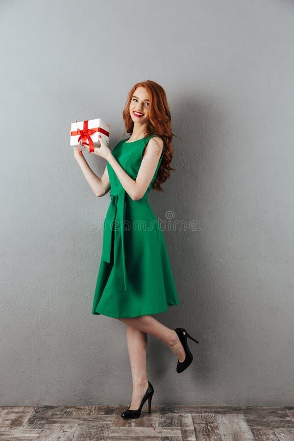 Vrolijke roodharige jonge vrouw in de groene gift van de kledingsholding stock afbeelding