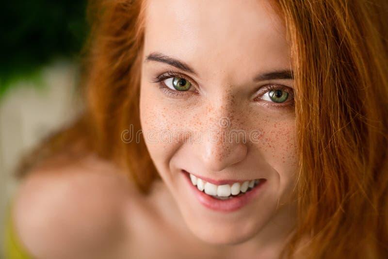 Vrolijke roodharigevrouw die met sproeten bij camera lachen stock foto