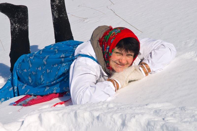 Vrolijke Russische vrouw in sundress die in de sneeuw liggen stock afbeeldingen