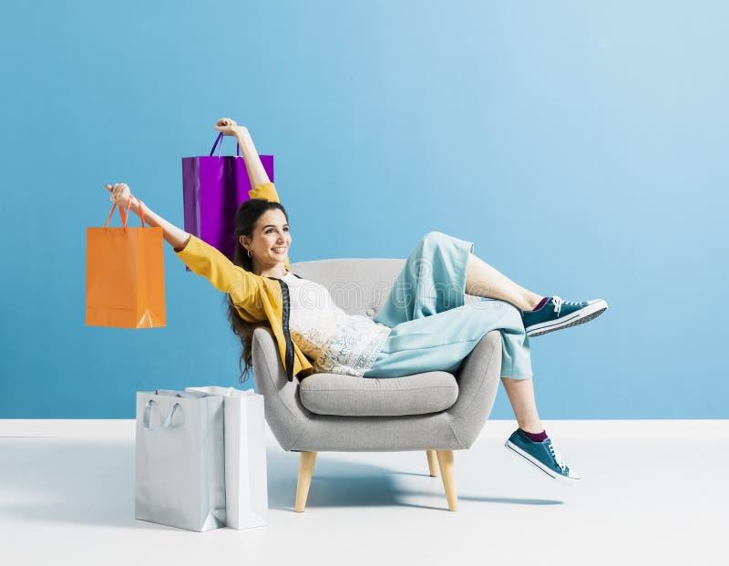 Vrolijke shopaholic vrouw met het winkelen zakken stock fotografie