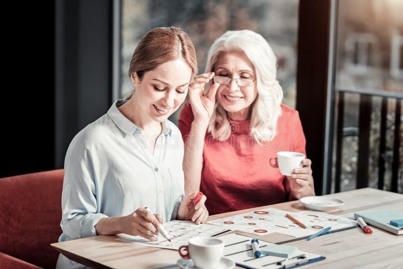 Vrolijke slimme vrouwen die nota's in een kalender en het glimlachen maken royalty-vrije stock foto
