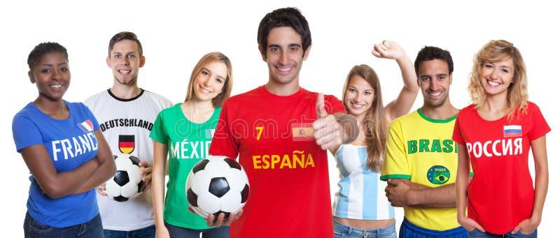 Vrolijke Spaanse voetbalventilator met het toejuichen van groep andere ventilators stock afbeeldingen