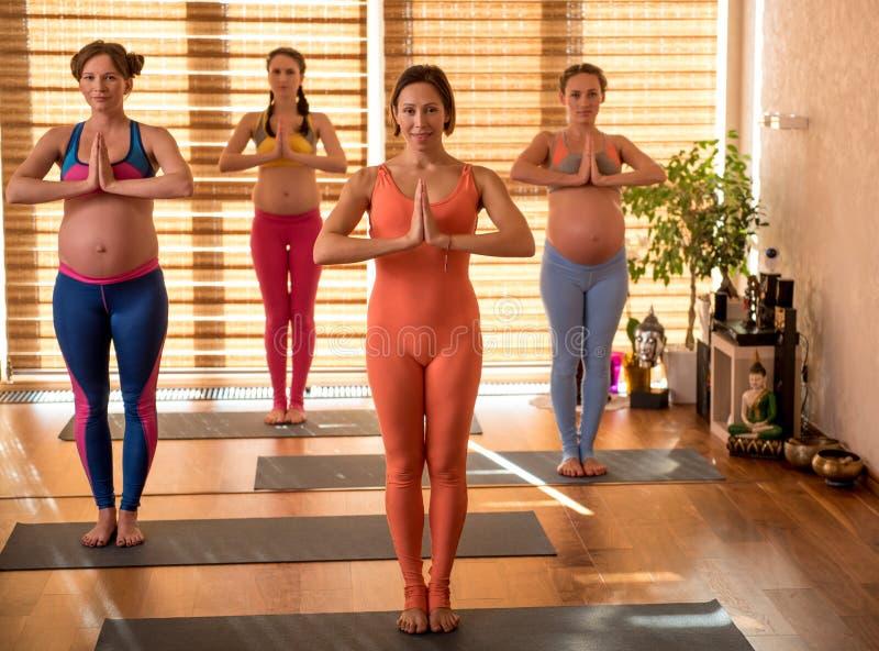 Vrolijke sportieve toekomstige mamma's die yoga doen stock fotografie