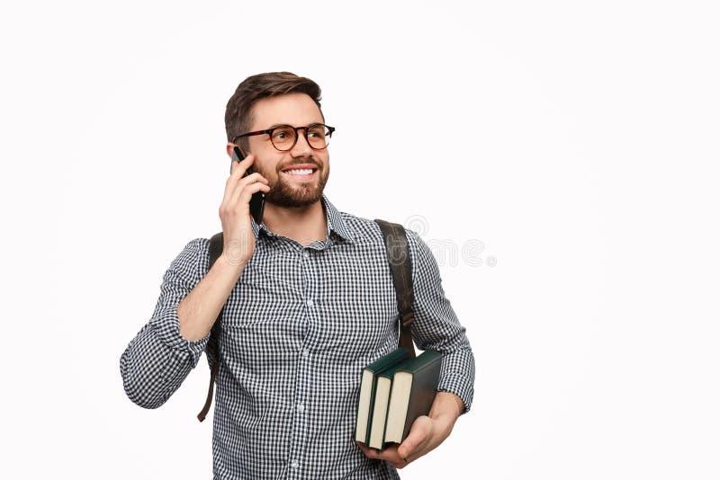 Vrolijke student die met boeken weg kijken stock foto