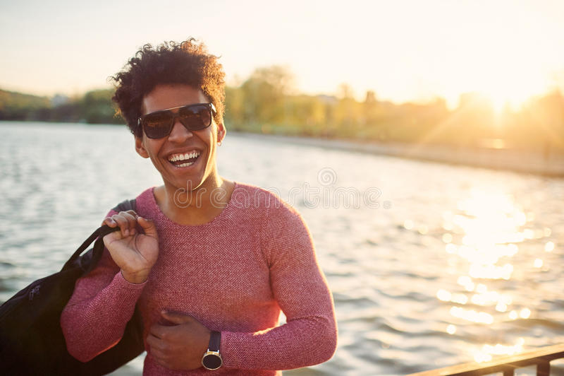 Vrolijke student die zonnebril dragen die dichtbij een meer glimlachen stock afbeeldingen