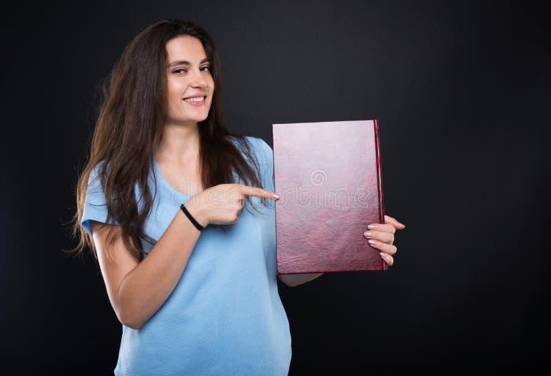 Vrolijke studente die op haar album richten royalty-vrije stock afbeeldingen