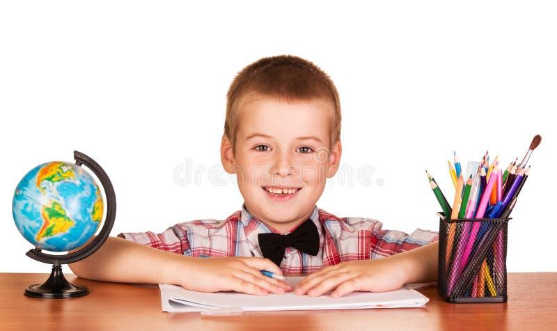 Vrolijke studentenzitting bij geïsoleerde lijst, kleurpotloden en bol stock foto