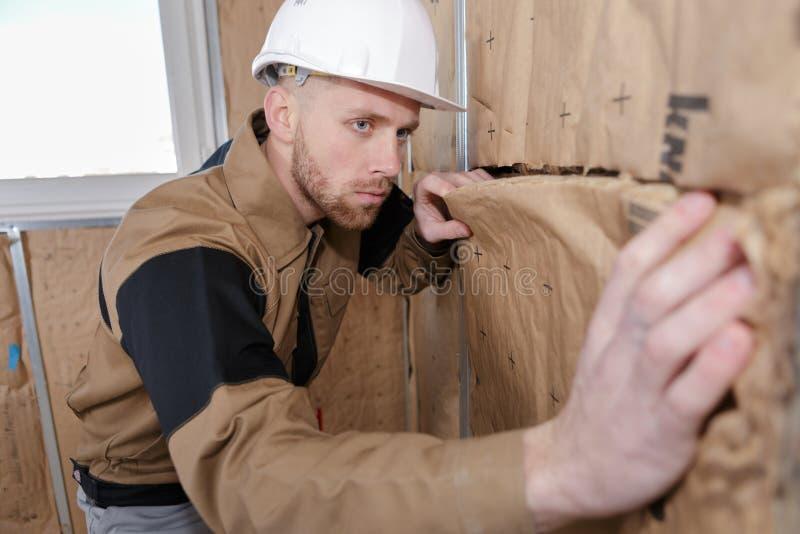 Vrolijke stukadoorarbeider aan binnen de werk van de muurisolatie stock afbeelding