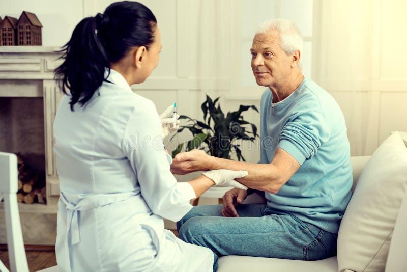 Vrolijke teruggetrokken mens die medische arbeider bekijken die hem inenten stock afbeelding