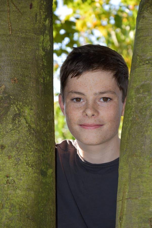 Vrolijke tiener die zich achter een boom bevinden royalty-vrije stock foto