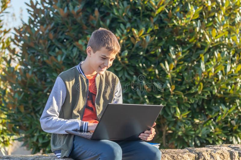 Vrolijke tienerjongen met laptop en handboeken die thuiswerk doen en voor een examen in het park voorbereidingen treffen royalty-vrije stock afbeeldingen