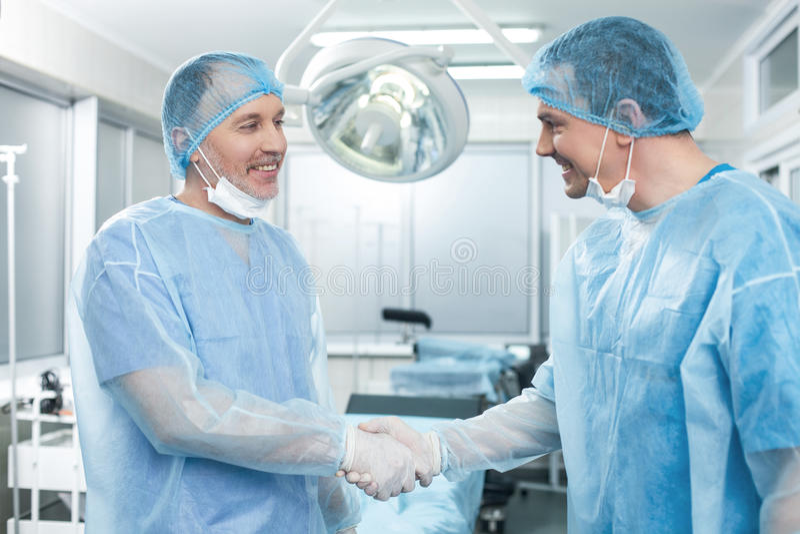 Vrolijke twee artsen die elkaar met handdruk gelukwensen royalty-vrije stock foto